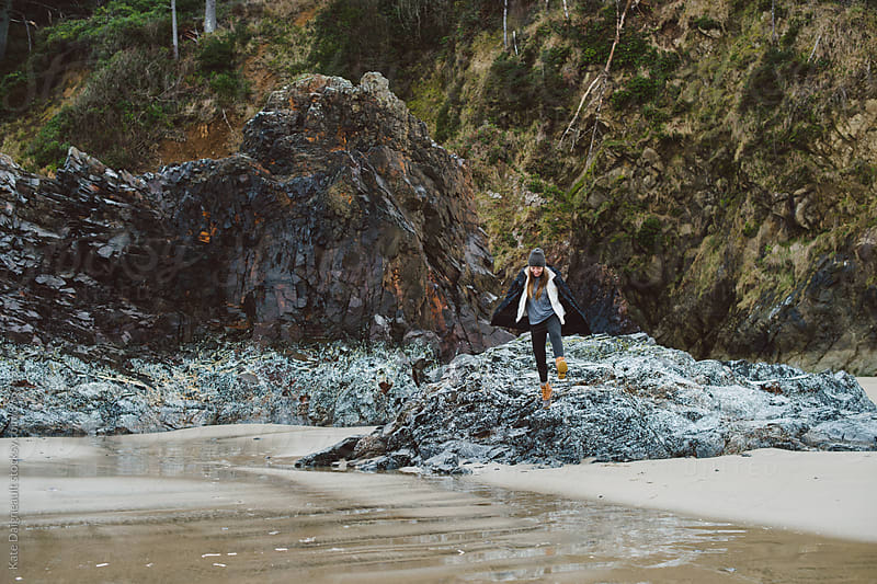 Young woman playing on barnacled covered rocks at the beach by Kate Daigneault for Stocksy United