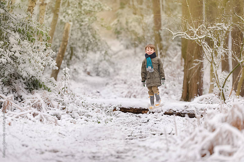 Boy playing in snowy woods by Rebecca Spencer for Stocksy United
