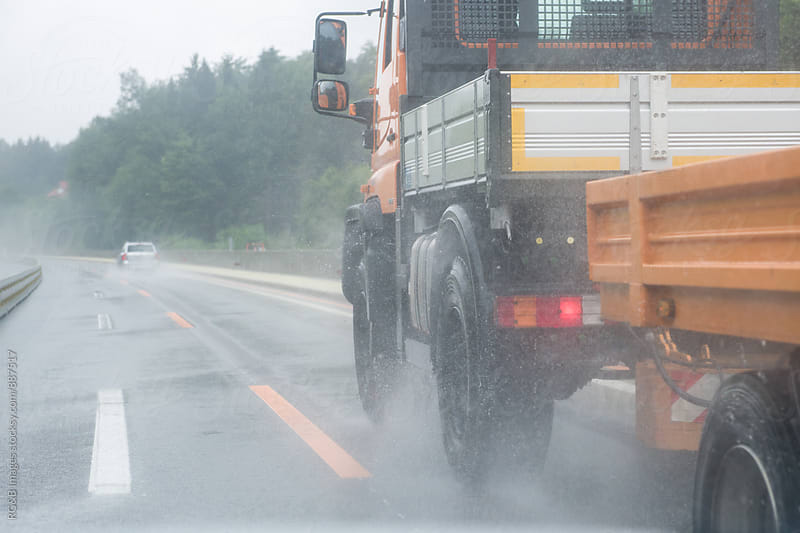 Truck speeding on the road on rainy day by RG&B Images for Stocksy United
