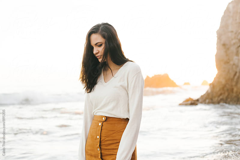 Young Woman On Beach by Caleb Thal for Stocksy United