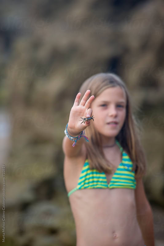 Girl holding a crab on the beach by Marta Muñoz-Calero Calderon for Stocksy United