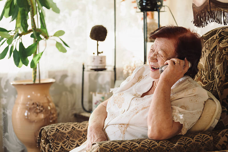 Happy senior woman talking on cellphone laughing by Ilya for Stocksy United