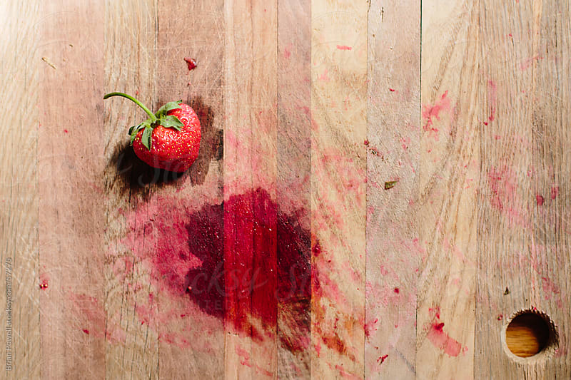 strawberry on wood cutting board by Brian Powell for Stocksy United