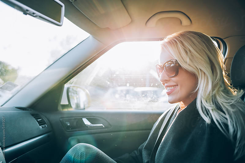 Smiling Blonde Woman in a Car by Lumina for Stocksy United