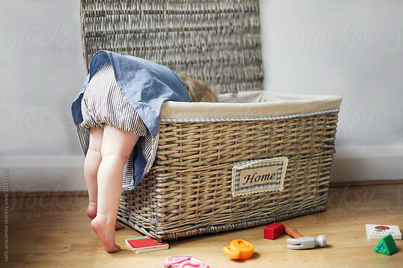 Child looking for toys in a toy box by sally anscombe for Stocksy United