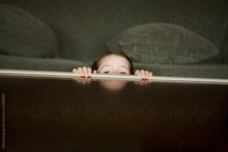 Little Girl Peeking Over Wooden Table by Dina Giangregorio for Stocksy United