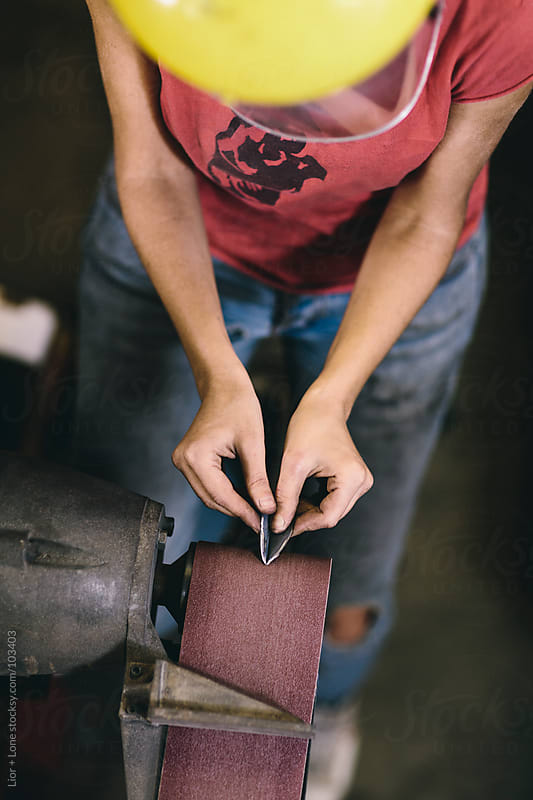Young working woman sanding steel on belt sander by Lior + Lone for Stocksy United