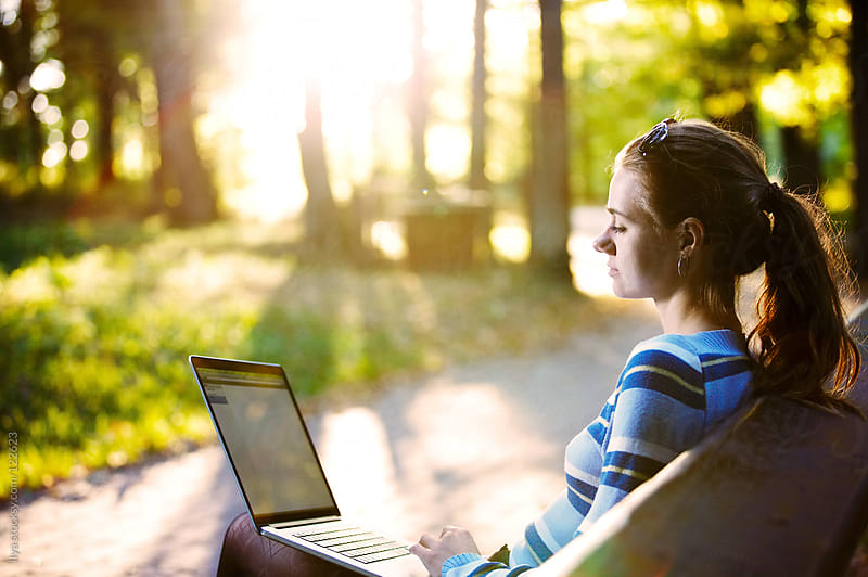Young woman using laptop in park by Ilya for Stocksy United