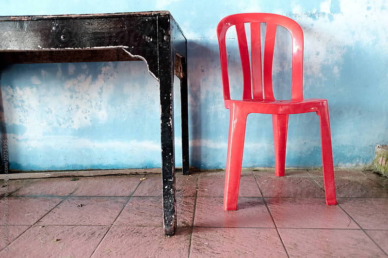 Red Plastic Chair and Wooden Table Oriented Horizontally by Gary Radler Photography for Stocksy United