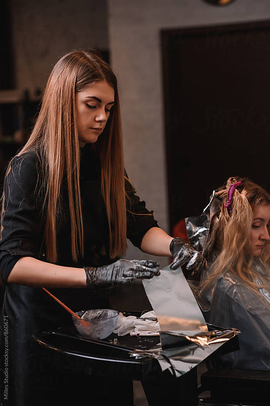 Hairdresser dyeing girl's hair by Milles Studio for Stocksy United