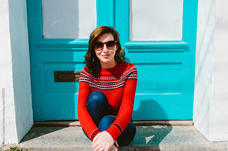 A woman sitting on the doorstreps wearing sunglasses by Kristen Curette Hines for Stocksy United