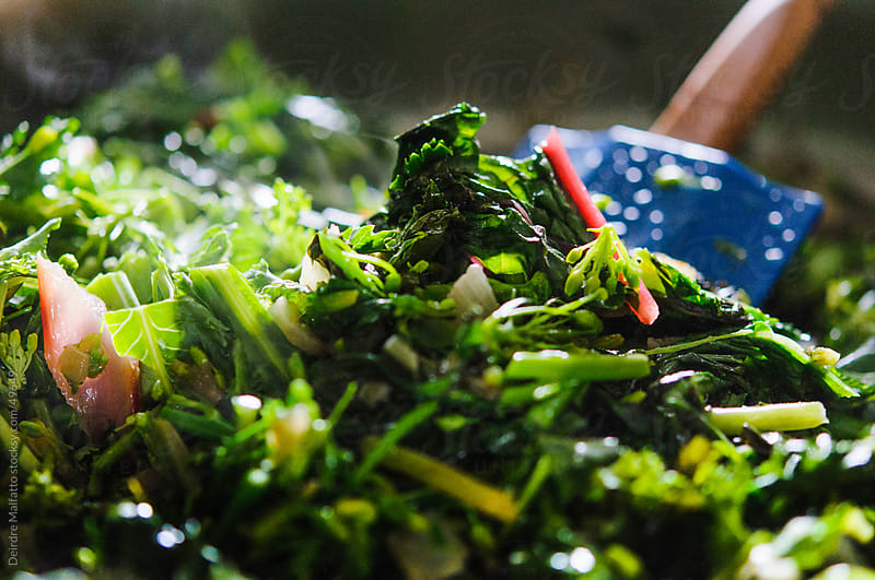 Kale raab, chard,  and other spring greens being cooked and stirred by Deirdre Malfatto for Stocksy United