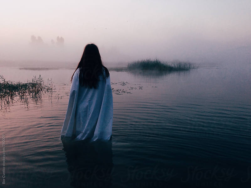 Woman in lake at sunrise by Bor Cvetko for Stocksy United