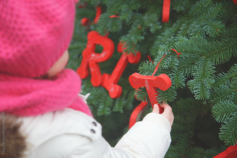 A girl holds the letter T that hangs from a decorated Christmas tree by Tana Teel for Stocksy United
