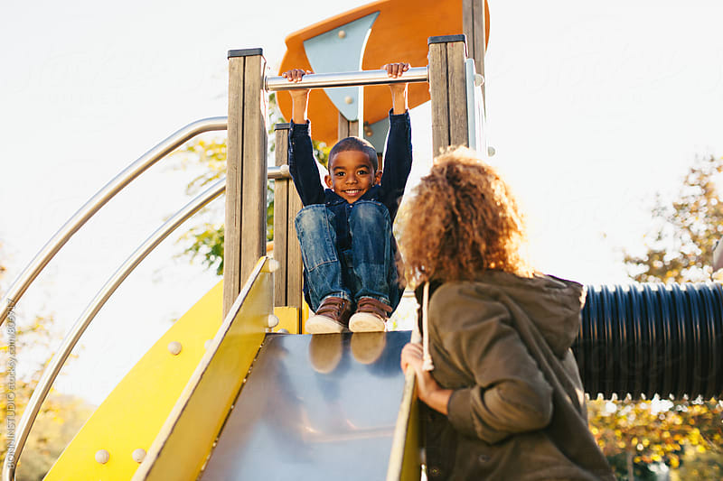 A 5 years old boy playing with his mother on a yellow slide. by BONNINSTUDIO for Stocksy United