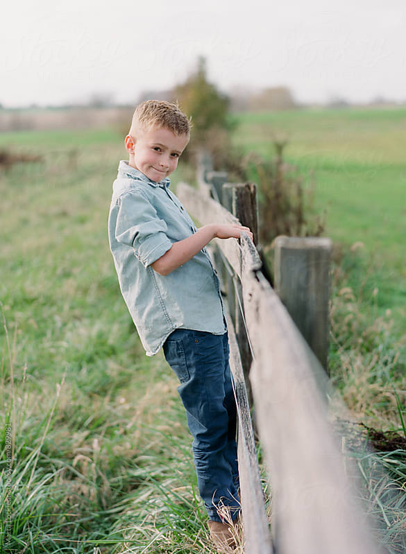 Boy climbing on an old fence by Marta Locklear for Stocksy United