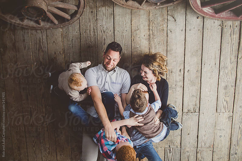 Family having fun tickling on old wood floor by Rob and Julia Campbell for Stocksy United