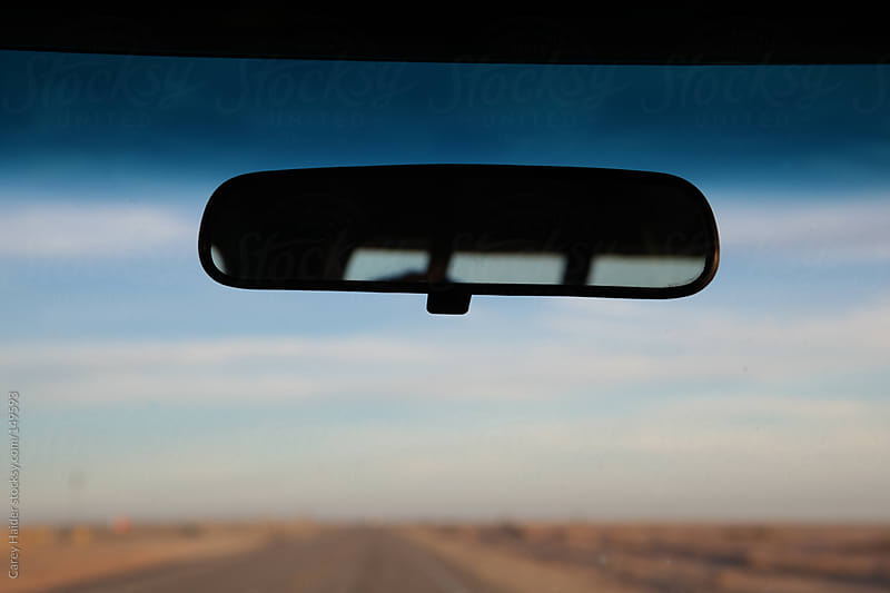 Rear View Mirror In A Vehicle Driving In The Desert by Carey Haider for Stocksy United