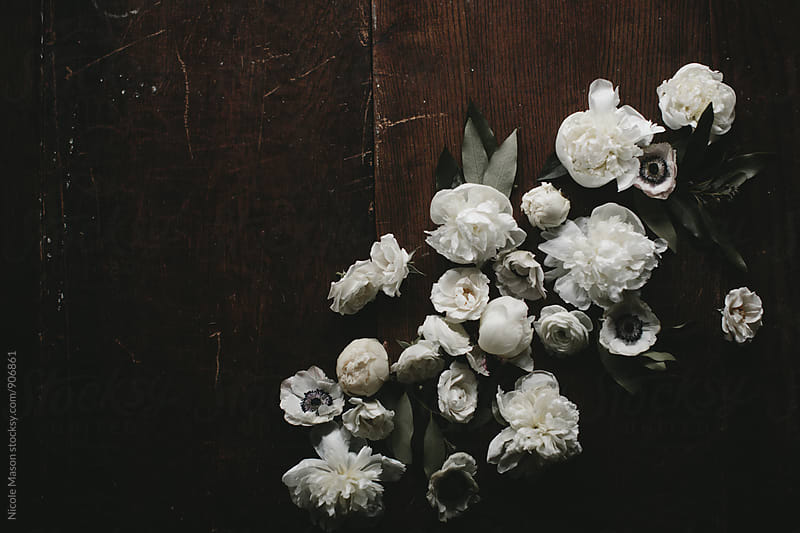 White flowers on dark wood table by Nicole Mason for Stocksy United