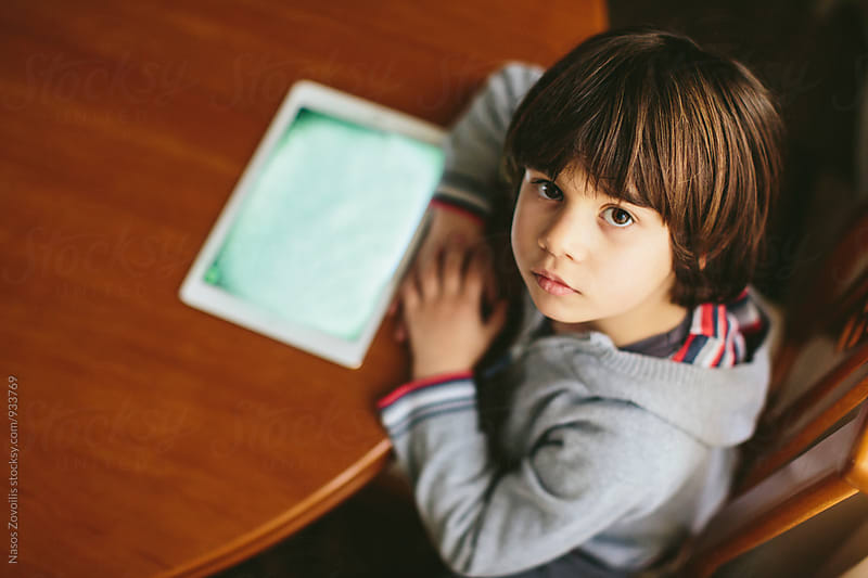 Small boy using a digital tablet by Nasos Zovoilis for Stocksy United
