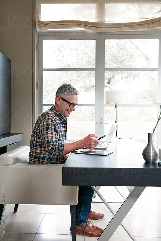 Mature man with grey hair working in home office by Trinette Reed for Stocksy United