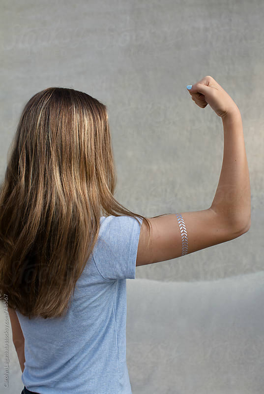 Confident teenage girl flexing her arm - girl power by Carolyn Lagattuta for Stocksy United