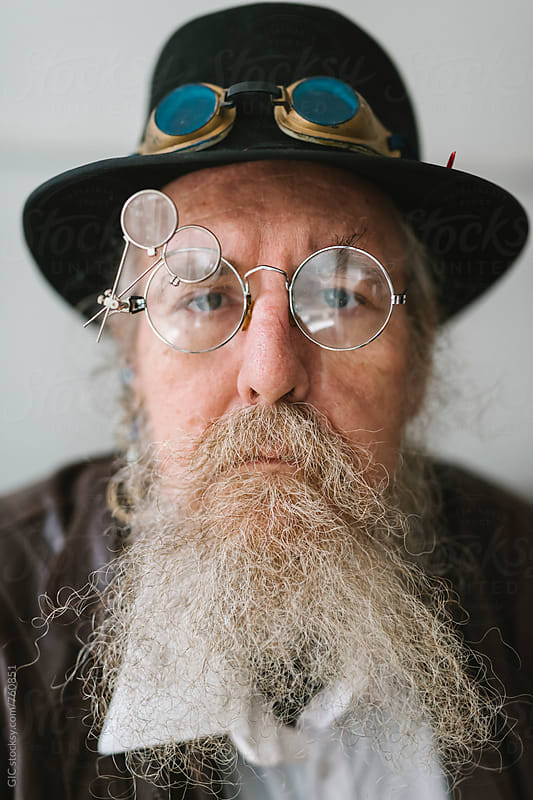 Stylish man with long beard and vintage glasses by Simone Becchetti for Stocksy United