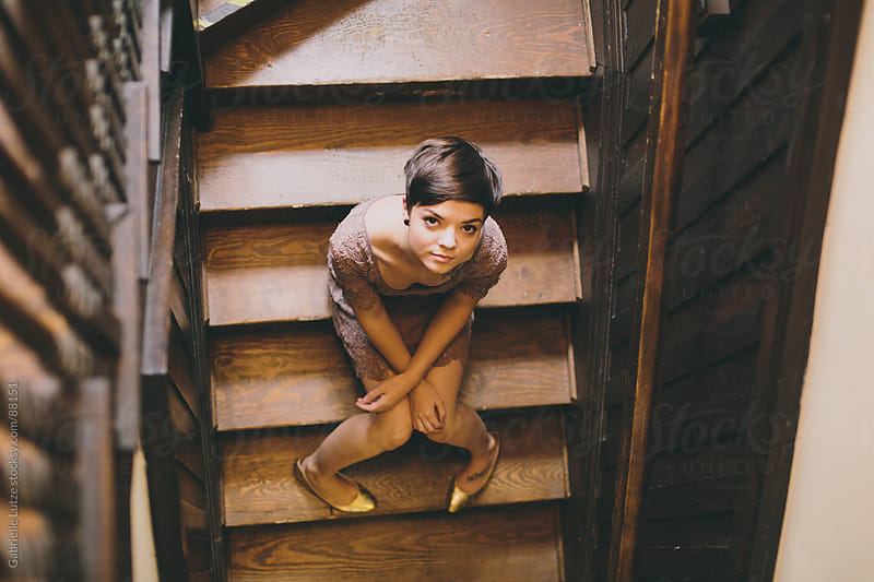 Girl sitting on wood stairs looking up by Gabrielle Lutze for Stocksy United