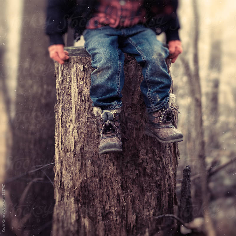 Young Boy Sitting on Tree Stump by Kevin Keller for Stocksy United