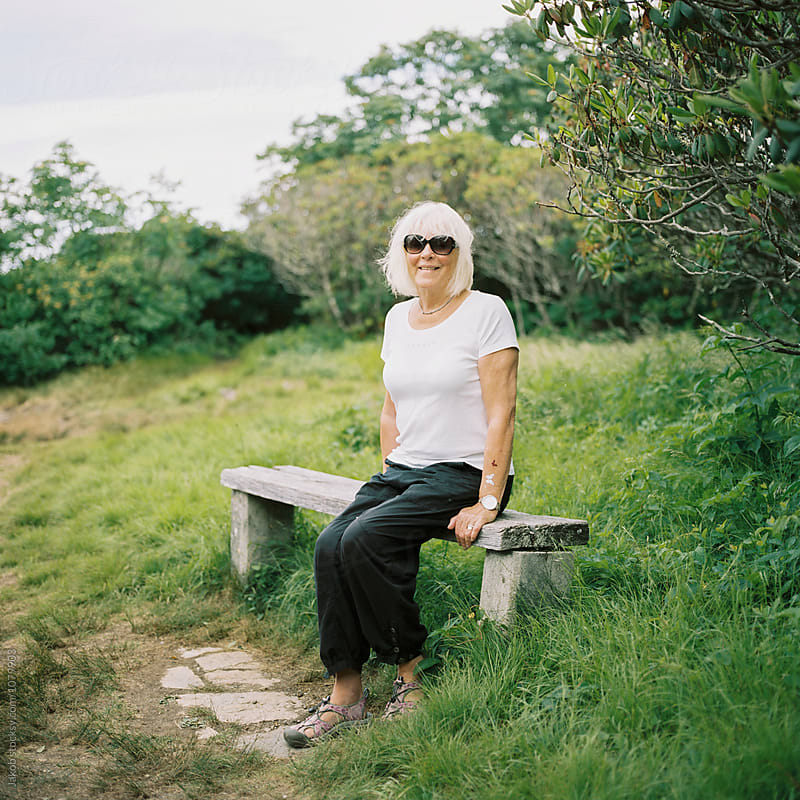 Old woman sitting on a bench taking  a break from hiking by Jakob for Stocksy United