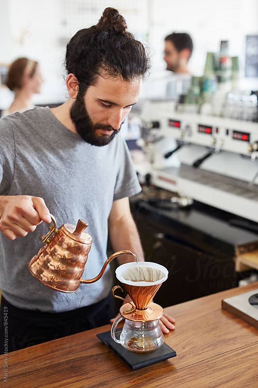 Barista pouring hot water into chemex by Martí Sans for Stocksy United