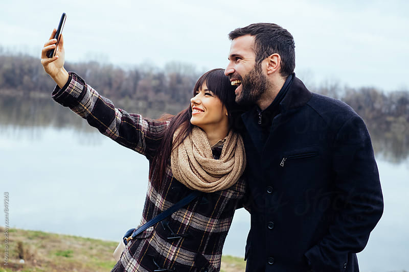 Couple Taking Selfies in Nature on a Winter Day by Mosuno for Stocksy United