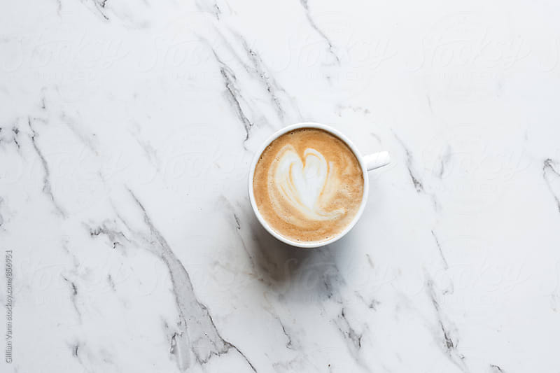 flat white coffee with a loveheart shape, on a marble background by Gillian Vann for Stocksy United