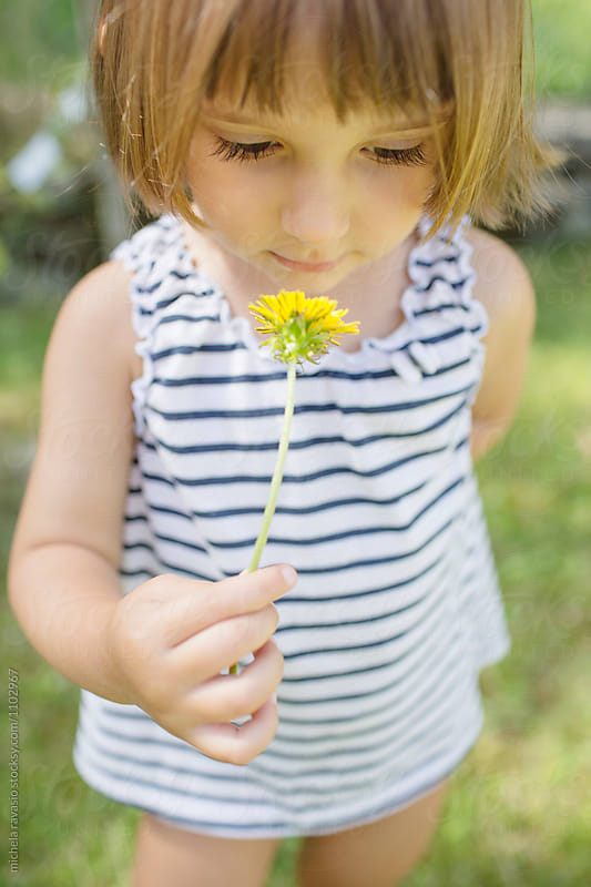 Little girl holding yellow flower