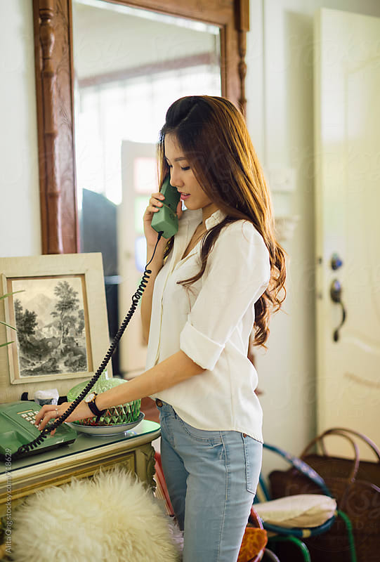 A woman making phone call at home by Alita Ong for Stocksy United