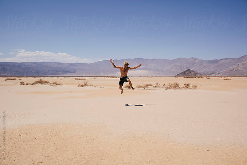 Man jumping for joy in the desert by Gary Parker for Stocksy United