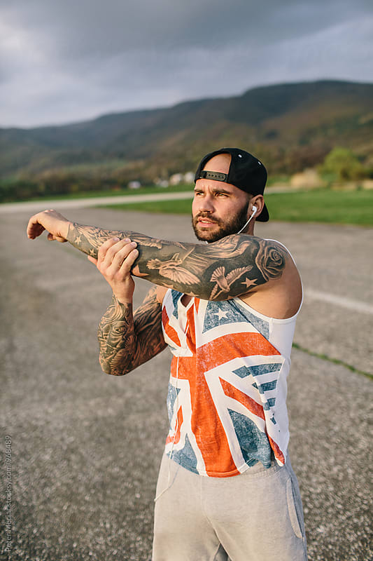 Sporty Tattooed Man Stretching by Peter Meciar for Stocksy United