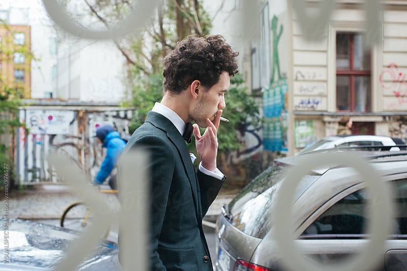 Stylish Young Man in Suit Smoking Cigarette Outdoors by VISUALSPECTRUM for Stocksy United