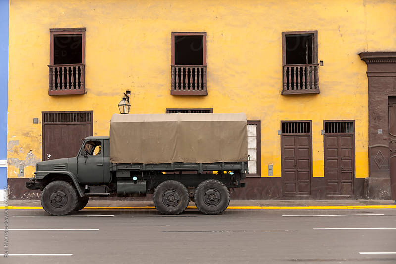 Modern army truck in front of spanish colonial facade by Ben Ryan for Stocksy United