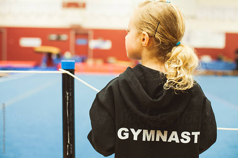 A little gymnast stands at a competition. by Cherish Bryck for Stocksy United