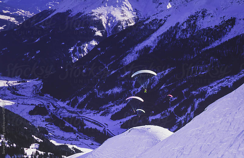 Paragliders flying in winter mountain landscape by Soren Egeberg for Stocksy United