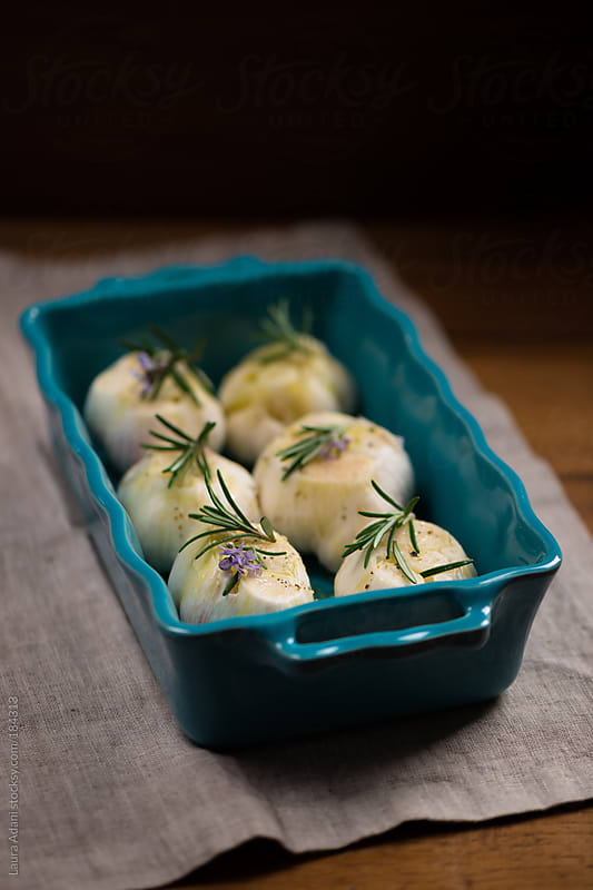 roasted garlic heads with rosemary and olive oil by Laura Adani for Stocksy United