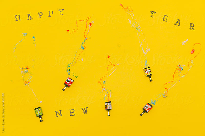 Party poppers popping on yellow background by Lior + Lone for Stocksy United
