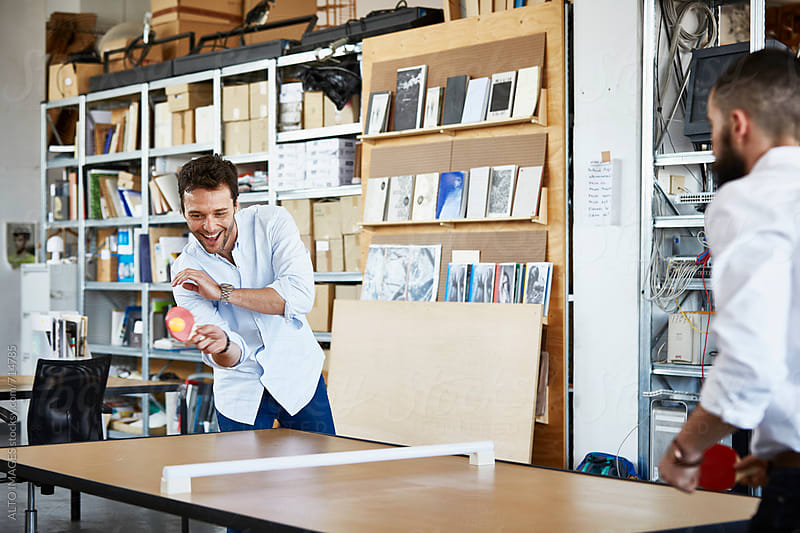 Businessmen Playing Table Tennis In Office by ALTO IMAGES for Stocksy United