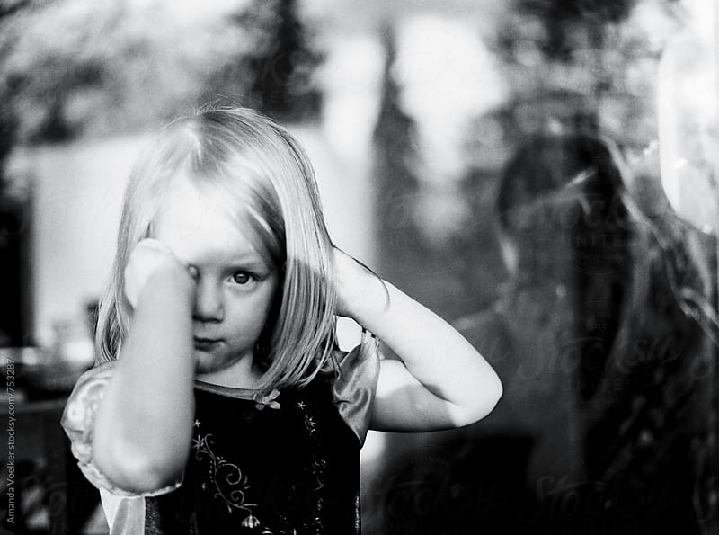 Young Girl Looking Through a Dirty Window by Amanda Voelker for Stocksy United