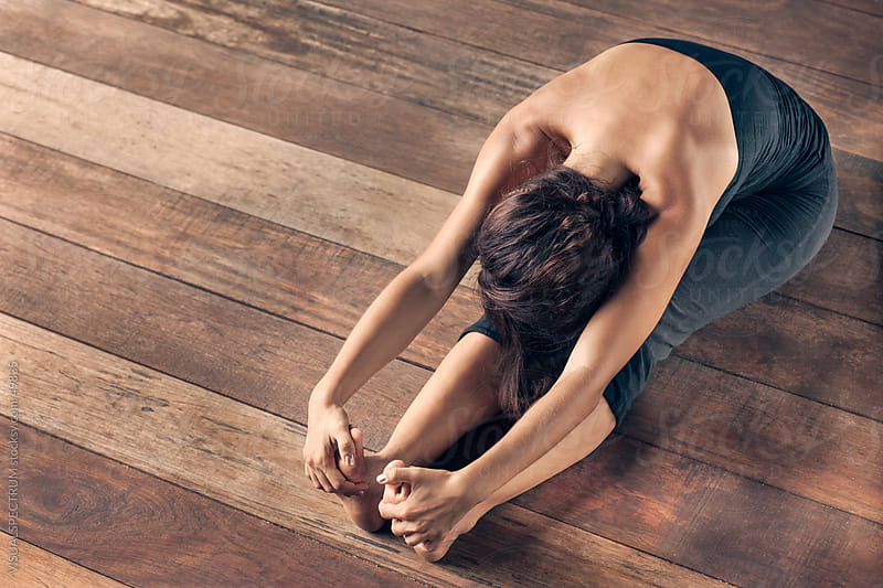 Yoga: Young Woman Doing Forward Bend by VISUALSPECTRUM for Stocksy United