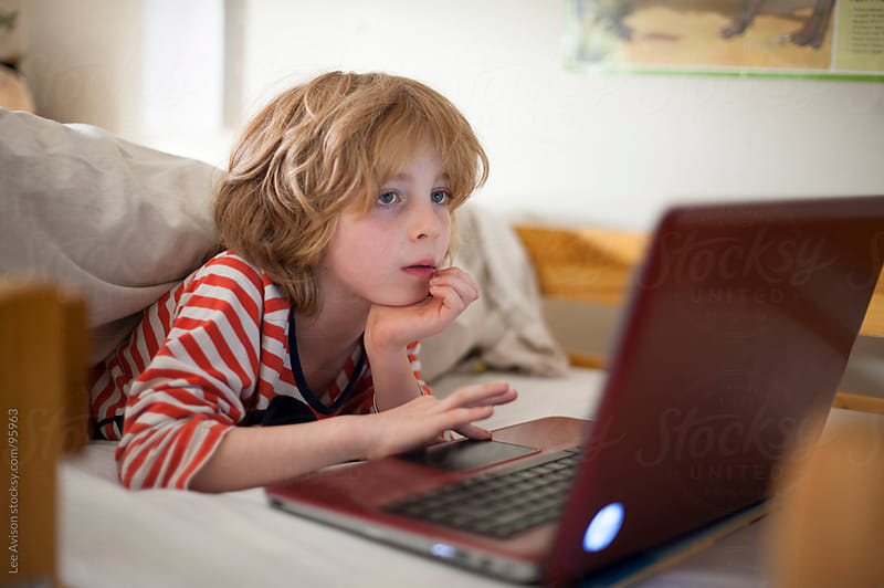 boy using a laptop in bed by Lee Avison for Stocksy United