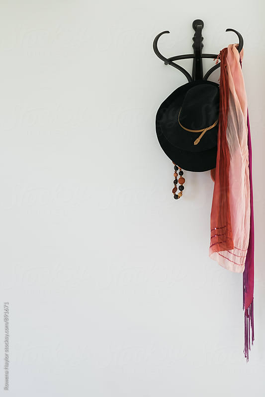 Hat stand on white wall with copy space by Rowena Naylor for Stocksy United