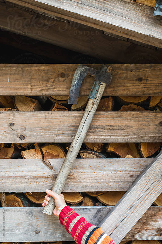 Hand holding axe by Pixel Stories for Stocksy United