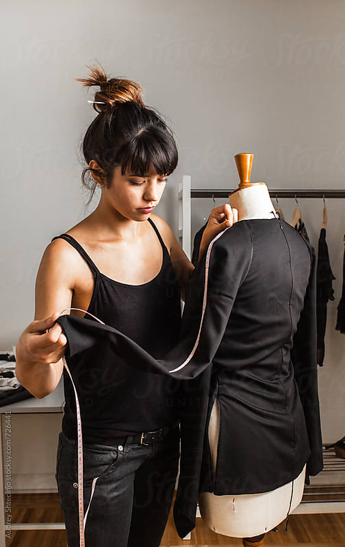 young fashion designer measuring sleeves on her new creation. by Audrey Shtecinjo for Stocksy United